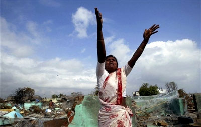A woman extends her arms to the sky as she grieves the loss of her child